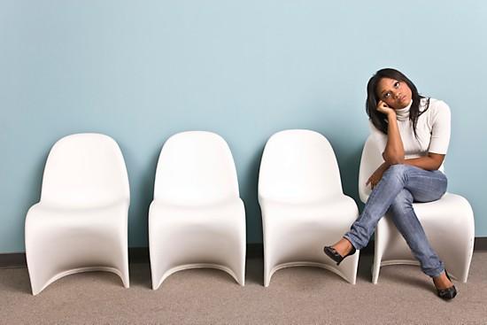 Girl sitting on white chair in waiting room, legs crossed.