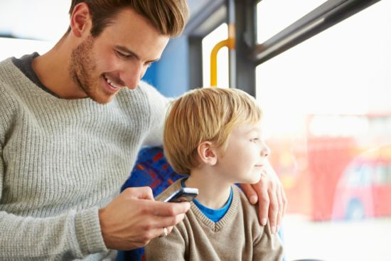 Man looking at smartphone while hanging with son.
