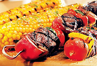 Beef tenderloin kebobs with grilled corn and fresh herb butter