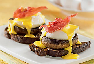 Eggs benedict on a bed of portobello mushroom with crispy prosciutto
