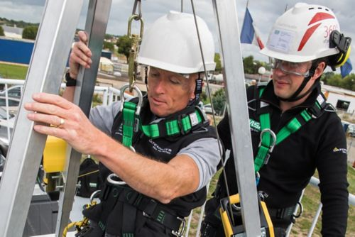 An industrial worker uses an MSA training tripod to descend into a confined space during training