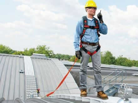 Safety worker talking on walkie talkie while anchored to rooftop with personal fall protection and engineered roofing system