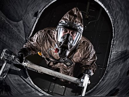 An industrial worked in a confined space climbs a ladder while wearing an industrial SCBA.