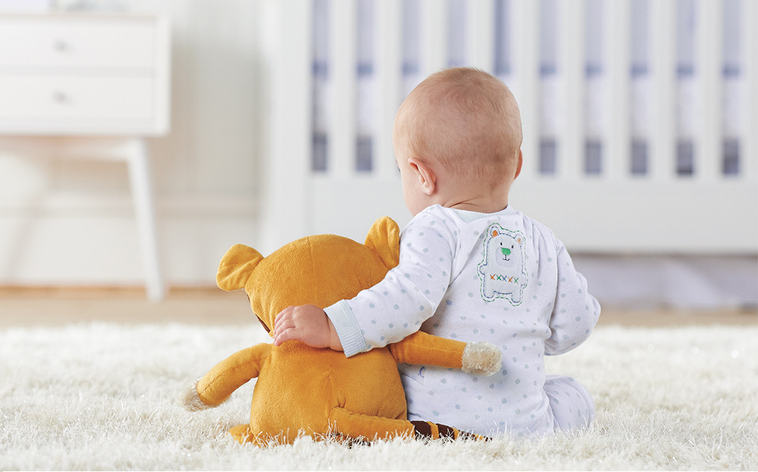 Baby sitting with stuffed animal