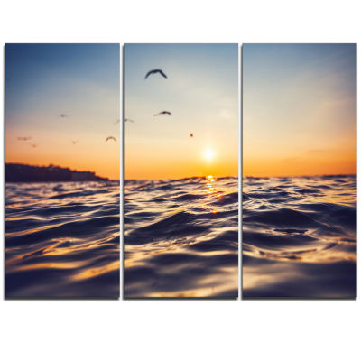 Designart Orange Tinged Sea Waters At Sunrise Beach Photo Triptych Canvas Print