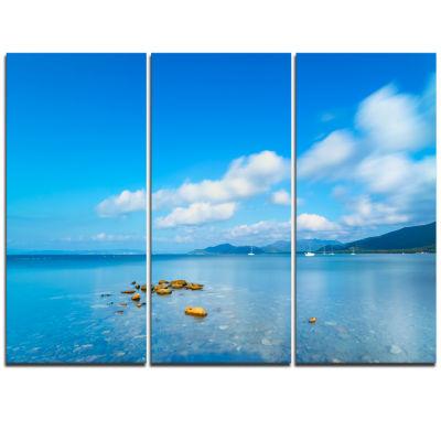 Designart Rocks In A Blue Panoramic Sea Bay ExtraLarge Seashore Triptych Canvas Art