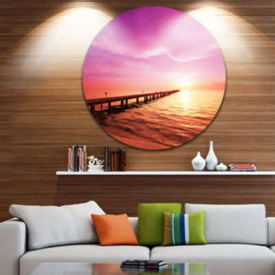 Design Art Brown Sea and Pier under Magenta Sky Bridge Metal Circle Wall Art