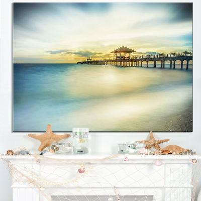Designart Blue Tinged Seashore With Distant Pier Canvas Art