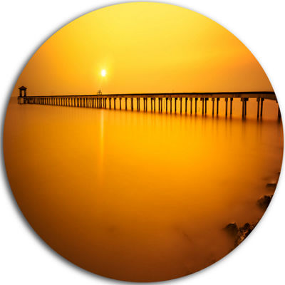 Design Art Yellow Tinged Seashore and Long Pier Pier Seascape Metal Circle Wall Art