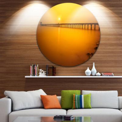 Design Art Yellow Tinged Seashore and Long Pier Pier Seascape Metal Circle Wall Art