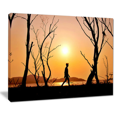 Designart Man Walking Alone In Evening LandscapePhotography Canvas Print