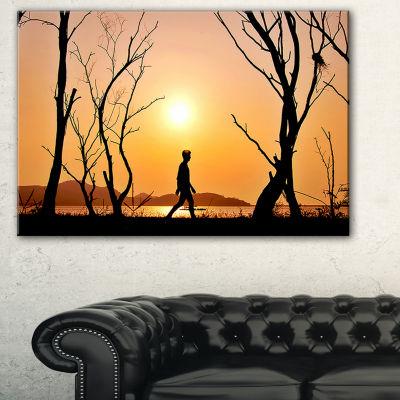 Designart Man Walking Alone In Evening LandscapePhotography Canvas Print
