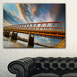 Designart Old Bridge Over River On Cloudy Day Canvas Art