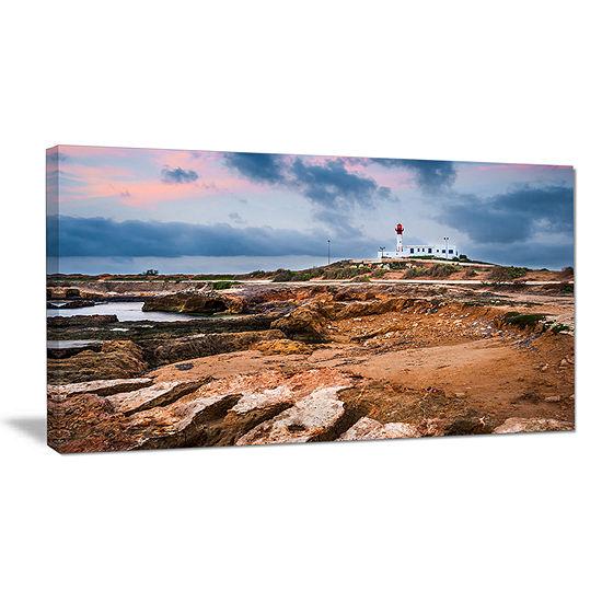 Designart Remote Lighthouse On The Rocks Canvas Art