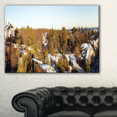 Designart Rocky Coast With Wooden Cottage Canvas Art