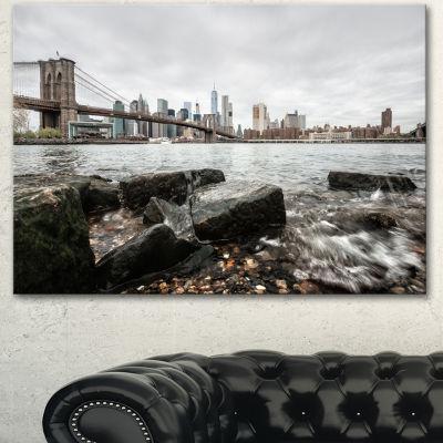 Designart Brooklyn Bridge With Rocks On Shore Large Cityscape Canvas Art Print