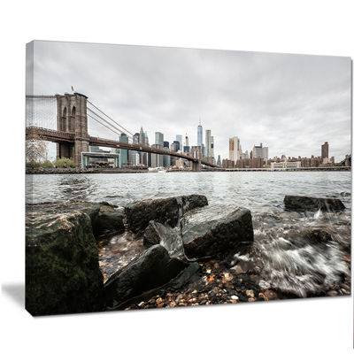 Designart Brooklyn Bridge With Rocks On Shore Large Cityscape Canvas Art Print