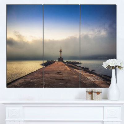Designart Lighthouse On Coast And Cloudy Sky Modern Canvas Art Print - 3 Panels