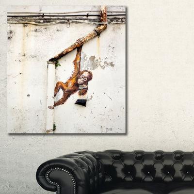Designart Baby Orangutan Hanging From Pipe StreetArt Canvas Art Print