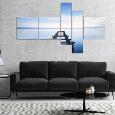 Designart Jetty Remains In Blue Lake Multipanel Seascape Canvas Art Print - 4 Panels