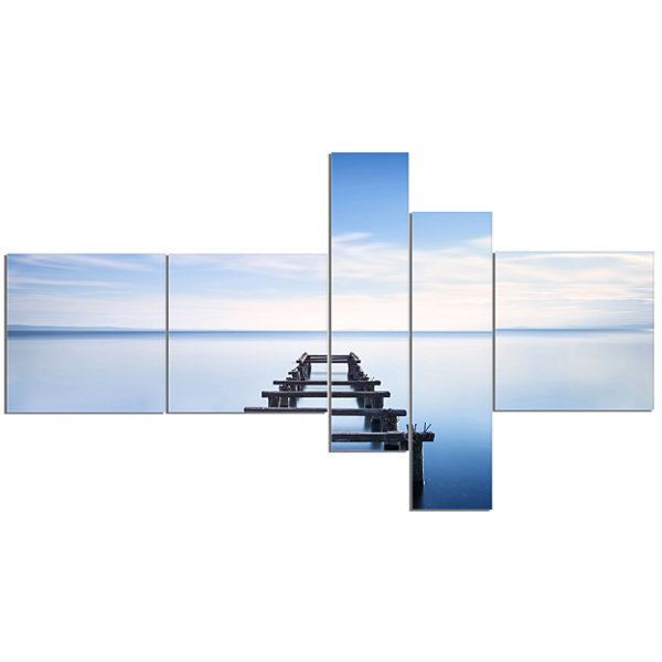 Designart Jetty Remains In Blue Lake Multipanel Seascape Canvas Art Print - 5 Panels