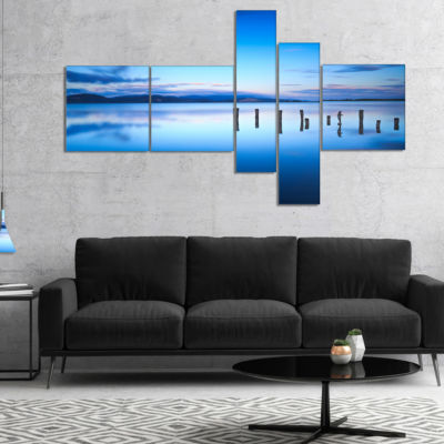 Designart Jetty Remains In Blue Sea Multipanel Seascape Canvas Art Print - 5 Panels