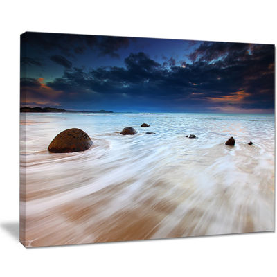 Designart Waves Flowing Over Boulders Seashore Photo Canvas Art Print