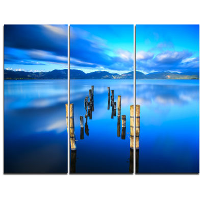 Designart Wooden Pier Remains In Blue Sea SeascapeCanvas Art Print - 3 Panels