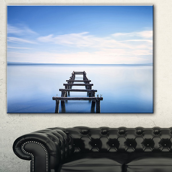 Designart Jetty Remains In Blue Lake Seascape Canvas Art Print - 3 Panels