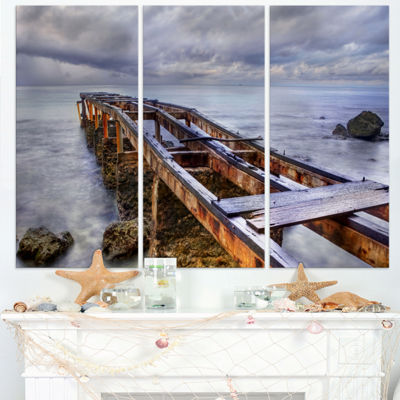 Designart Old Rusty Pier In Cloudy Day Seashore Photo Canvas Art Print - 3 Panels