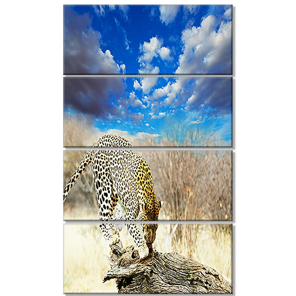 Designart Leopard Feeding on Tree Trunk Extra Large AfricanCanvas Art Print - 4 Panels