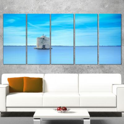 Designart Old Spanish Windmill in Blue Lagoon Extra Large Seashore Canvas Art - 4 Panels