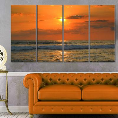 Designart Orange Tinged Tropical Sunset and WavesBeach Photo Canvas Print - 4 Panels