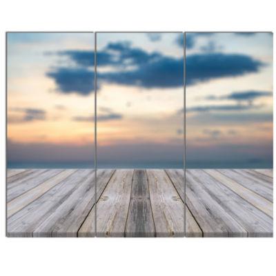 Designart Wooden Board At Sunset Seashore ModernCanvas Art Print - 3 Panels