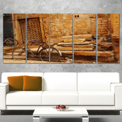Designart Bicycle Against Brown Wall Landscape Photo Canvas Art Print - 5 Panels