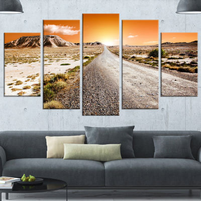 Designart Sunset Desert With Pebble Road LandscapeCanvas Art Print - 4 Panels