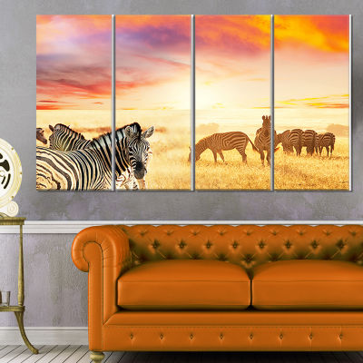 Designart Cute Zebras Grazing In Grassland AnimalCanvas Art Print - 4 Panels