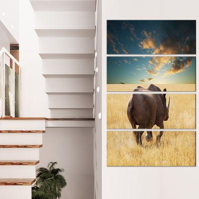 Designart Giant Rhino Under Cloudy Sky Extra LargeAfrican Canvas Art Print - 4 Panels