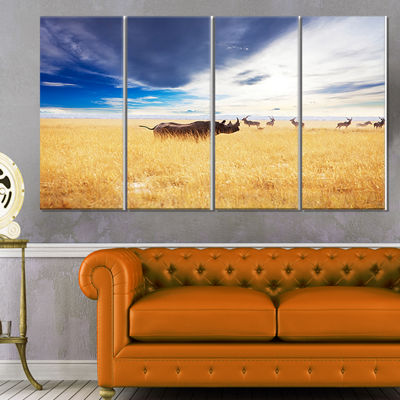 Designart Huge Rhino With Antelopes Seashore Canvas Art Print - 4 Panels