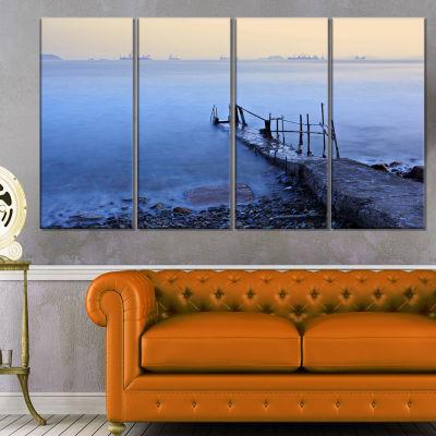 Designart Abandoned Pier into Blue Sea Sea BridgeCanvas Art Print - 4 Panels
