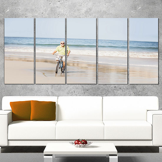 Designart Smiling Senior Man Riding Bike LandscapeCanvas Art Print - 4 Panels