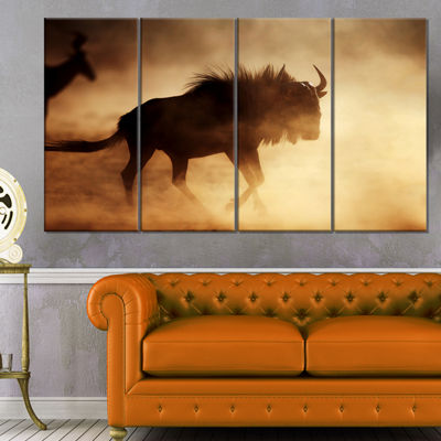 Designart Blue Wildebeest Running in Dust AfricanCanvas Art Print - 4 Panels