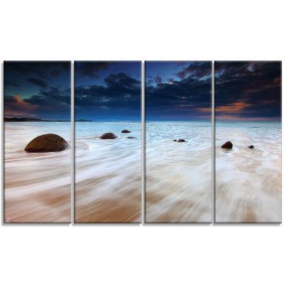 Designart Waves Flowing Over Boulders Seashore Photo CanvasArt Print - 4 Panels