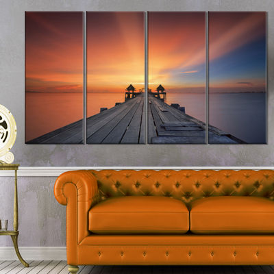 Designart Wooden Bridge Under Illuminated Sky PierSeascapeCanvas Art Print - 4 Panels