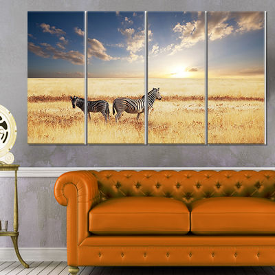 Designart Zebras in Beautiful Grassland at SunsetExtra Large African Canvas Art Print - 4 Panels