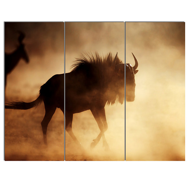 Designart Blue Wildebeest Running In Dust AfricanCanvas Art Print - 3 Panels