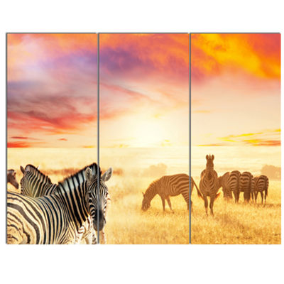 Designart Cute Zebras Grazing In Grassland AnimalCanvas Art Print - 3 Panels