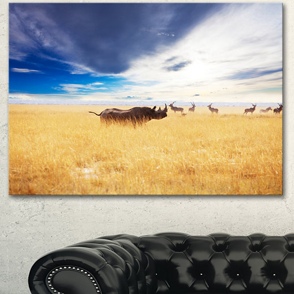 Designart Huge Rhino With Antelopes Seashore Canvas Art Print