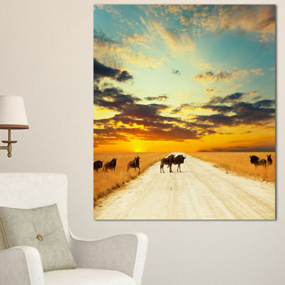 Designart Wildebeests Crossing Path In Evening African Landscape Canvas Art Print