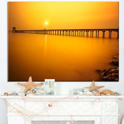Designart Yellow Tinged Seashore And Long Pier Canvas Art